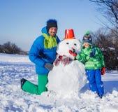 Jongen en zijn vader met een sneeuwman stock foto