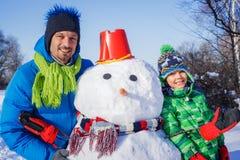 Jongen en zijn vader met een sneeuwman royalty-vrije stock foto's