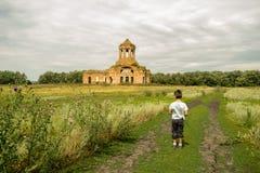 Jongen in groene weide met kerk op een backgroung Stock Foto's