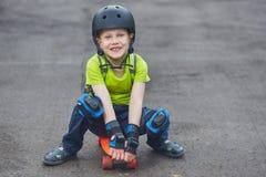 Jongen in helm het stellen met skateboard Royalty-vrije Stock Fotografie