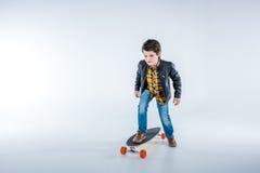 Jongen in het berijdende skateboard van het leerjasje op grijs Royalty-vrije Stock Foto