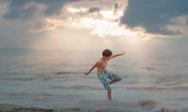 Jongen het bespatten in golven Stock Foto