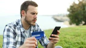 Jongen het betalen met creditcard en telefoon maakt fout stock videobeelden
