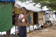 Jongen in het boek van de krottenwijkholding stock foto