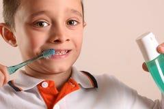 Jongen het borstelen tanden met tandenborstel op ge?soleerde bruin stock foto