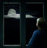 Jongen in het donkere venster die de heldere volle maan bekijken Royalty-vrije Stock Afbeelding