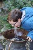 Jongen het drinken bij fontein Stock Foto's