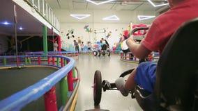 Jongen het karting in lokaal pretpark, auto van het kind de drijfpedaal op speelplaats, sportactiviteiten stock footage
