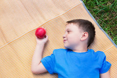 Jongen het leggen op mat en bekijkt appel Royalty-vrije Stock Foto
