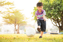 Jongen het leren schopbal bij het park in de avond Stock Afbeeldingen