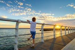 Jongen het letten op zonsondergang van St Kilda Jetty Royalty-vrije Stock Afbeeldingen