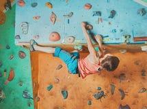 Jongen het praktizeren in het beklimmen van gymnastiek Stock Foto's