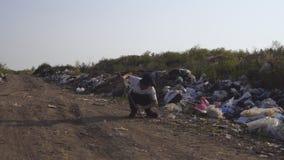 Jongen het schoppen het plastiek kan in stortplaats stock footage