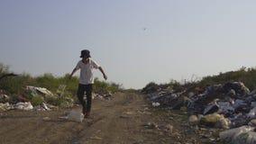 Jongen het schoppen het plastiek kan in stortplaats stock video