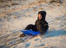 Jongen het sledding in de zonsondergangkleuren die de sneeuwafwijking proberen te vangen Stock Foto's