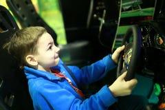 Jongen het spelen in autosimulator stock foto