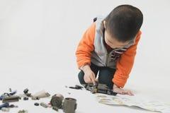 Jongen het spelen bakstenenstuk speelgoed met instructie royalty-vrije stock afbeelding