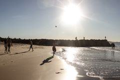 Jongen het spelen bal bij het strand terwijl andere mensen langs of vissen wandelen of de rotsen in recente middag - silhouetten  royalty-vrije stock foto's