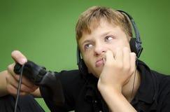 Jongen het Spelen BORED Videospelletjes - VERMOEID royalty-vrije stock afbeelding