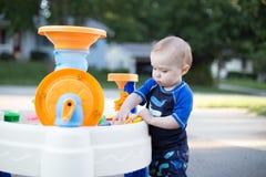 Jongen het spelen buiten in waterlijst stock afbeelding