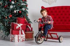 Jongen het spelen dichtbij Kerstboom Stock Afbeelding