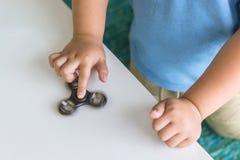 Jongen het spelen friemelt spinners stock foto
