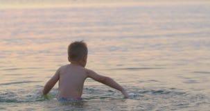 Jongen het Spelen in het Overzees bij Zonsondergang stock videobeelden