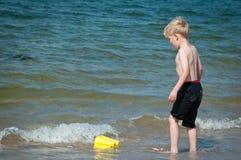 Jongen het spelen in het overzees met een gele buckey Stock Foto's