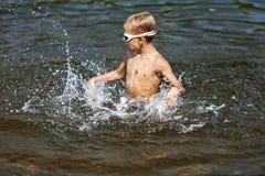 Jongen het spelen in het water (02) stock afbeeldingen