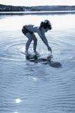 Jongen het spelen in het water stock afbeelding