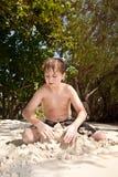 Jongen het spelen in het zand bij het strand tijdens vakantie Royalty-vrije Stock Afbeeldingen
