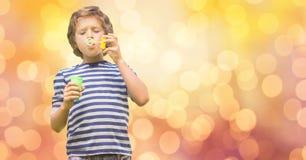 Jongen het spelen met bellentoverstokje over bokeh Royalty-vrije Stock Fotografie