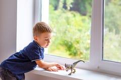 Jongen het spelen met dinosaurus thuis, dichtbij venster Kinderjaren stock foto