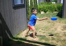 Jongen het spelen met een frisbee stock foto