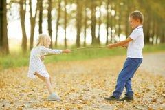 Jongen het spelen met een meisje in de herfstlandweg Royalty-vrije Stock Fotografie
