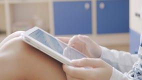 Jongen het spelen met een tablet in haar ruimtezitting op de vloer stock footage