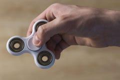 Jongen het spelen met friemelt spinnerstuk speelgoed Royalty-vrije Stock Foto's