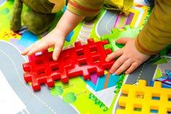Jongen het spelen met plastic blokken in huis Stock Foto