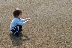 Jongen het Spelen met Rots Stock Afbeeldingen