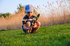 Jongen het spelen met windmolen in groen gras van het strand op het concept van de de zomervakantie voor vrijheid stock fotografie