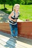 Jongen het spelen op een houten dia Stock Afbeelding