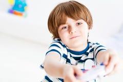 Jongen het spelen op een spelconsole Stock Afbeelding