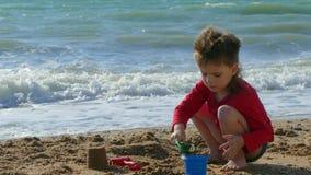 Jongen het spelen op het strand dichtbij het water stock video