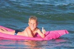 Jongen het spelen op het water stock foto's