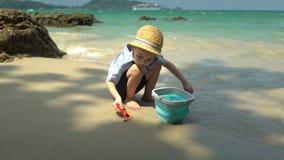 Jongen het spelen op het strand door het overzees hij graaft zand en werpt het in de emmer stock footage