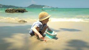 Jongen het spelen op het strand door het overzees hij graaft zand en werpt het in de emmer stock video
