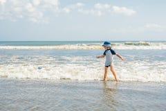 Jongen het spelen op het strand in het water stock foto