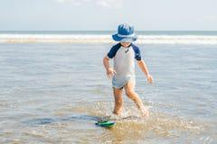 Jongen het spelen op het strand in het water stock afbeeldingen