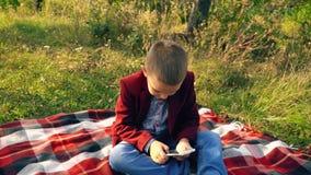 Jongen het spelen op telefoon in spelen stock videobeelden
