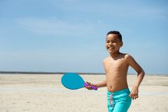 Jongen het spelen peddelbal bij het strand Royalty-vrije Stock Afbeelding